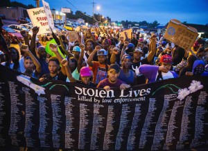 Protestors march and hold their fists aloft as they march during ongoing demonstrations in reaction to the shooting of Michael Brown in Ferguson, Missouri