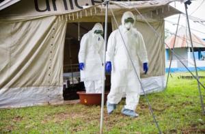 Un trabajador de la salud pone los pies en un recipiente de agua con hipoclorito de sodio, a la salida de una tienda de campaña de aislamiento durante un simulacro de ébola en el hospital de Biankouman, en Costa de Marfil. Crédito: Marc-André Boisvert/IPS