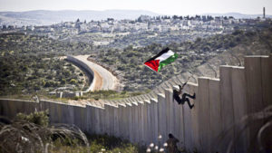 <p> A Palestinian youth places a flag on the Israeli wall during a protest marking 9 years for the struggle against the wall in the West Bank village of Bilin, February 28, 2014.</p>